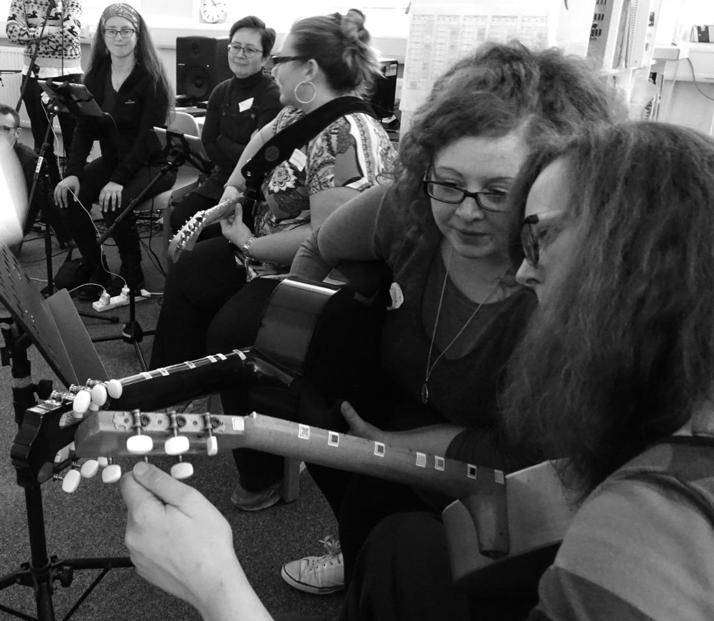 A group of women playing guitars and tuning them to Figurenotes tuning A E A E
