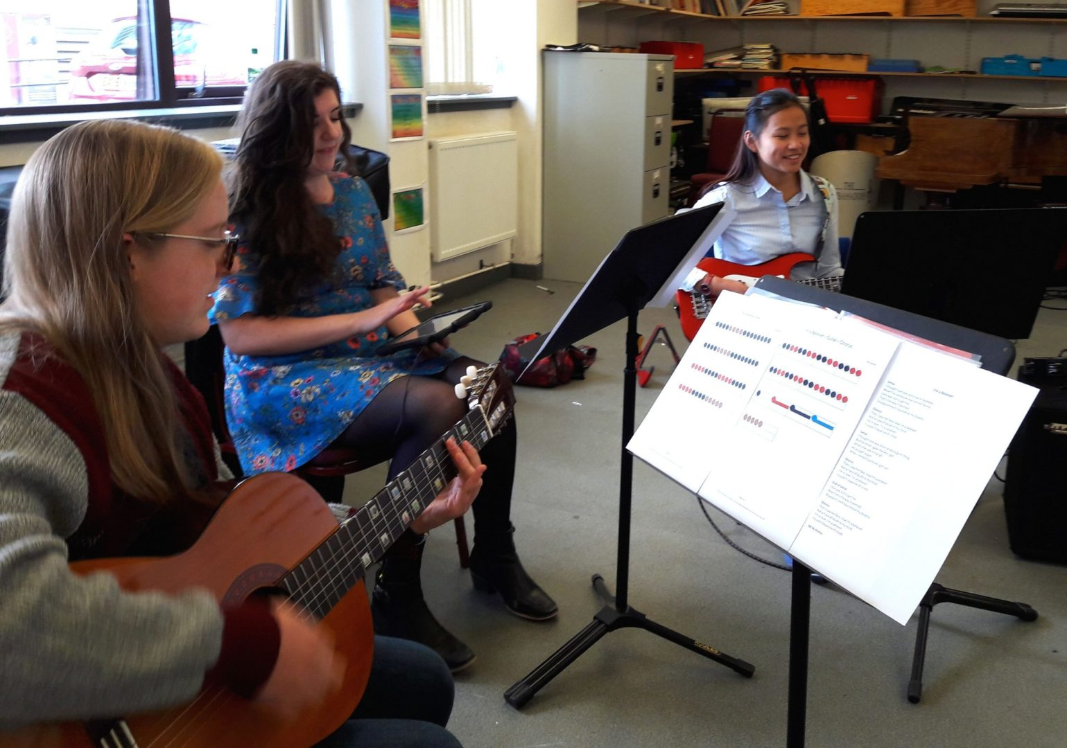3 women play in a band using Figurenotes notation. 1 on guitar, 1 on iPad, and 1 on bass guitar