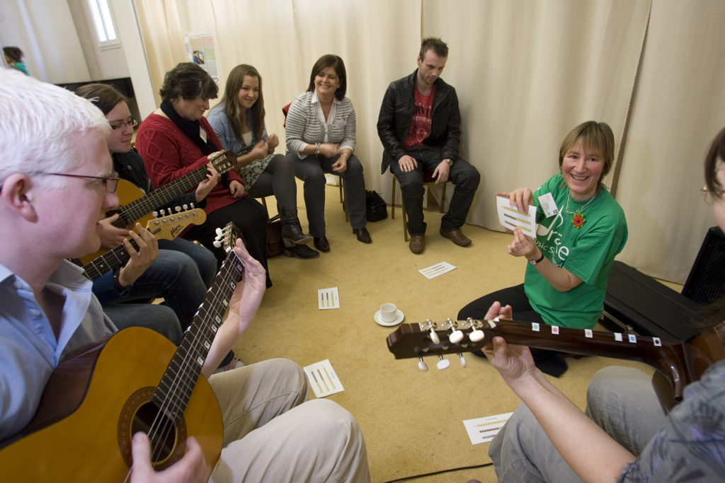 Jill demonstrates to a group of teachers, most of whom are playing guitars