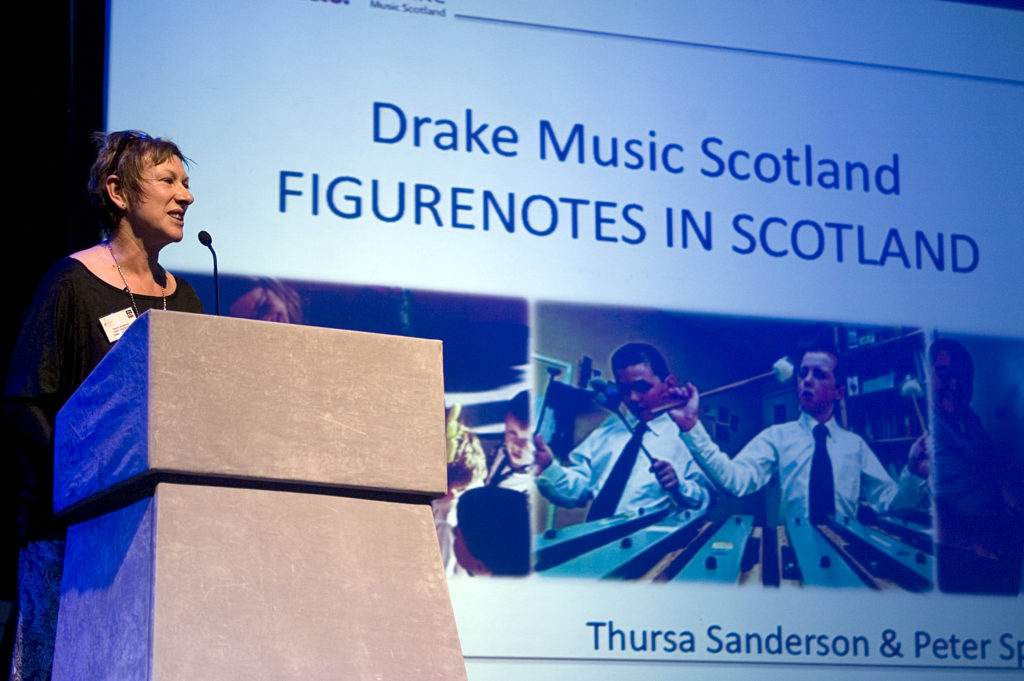 Thursa Sanderson presenting at the conference in front of screen reading 'Drake Music Scotland - Figurenotes in Scotland'