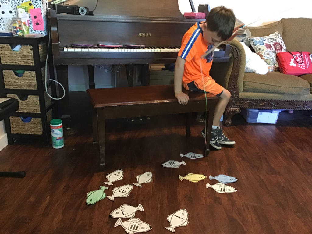 A child playing with paper fish in Figurenotes colours. The fish are spread on the floor. The child sits in front of the piano looking at the fish.