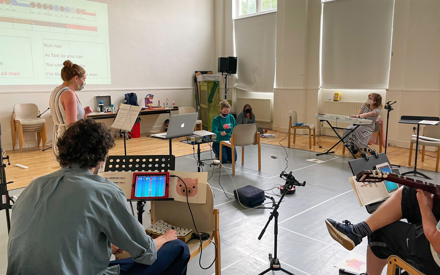 A group of musicians in a hall. A narrator is standing; seated woman on chimes; seated woman on keys; seated man with a pig flashcard, chimes, and an ipad showing Thumbjam. The edge of a guitar and its player can also be seen.